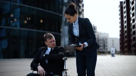 Young entrepreneur cripple business man in invalid wheelchair communicates with his woman lady colleague secretary assistant about documents in textpad. Wideo