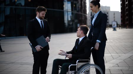 helpful : Young disabled entrepreneur businessman in wheelchair talking with his co-workers and signing important docs.