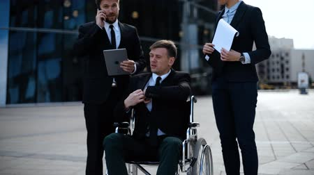 Businessman in a wheelchair with colleagues outside an office building discuss about deals.