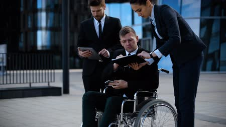 discutir : Businessman in a wheelchair with colleagues discuss abut deal and business. They work with textpad, tablet PC, mobile phone, selfphone and documents. Cripple people part of community. Vídeos