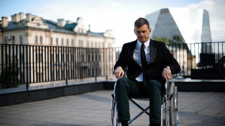 nervous breakdown : Disabled businessman trying to get up from wheelchair outdoor.