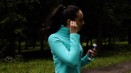 Happy sporty woman in headphones and handphone rapidly flexs outdoors in park asphalt running. Wideo