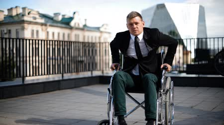 might : Handicapped businessman trying to get up from wheelchair outdoor.
