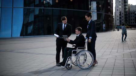 Businessman on wheelchair during meeting with female manager employee and partner entrepreneur outdoor. Disabled handicapped people in business. Wideo