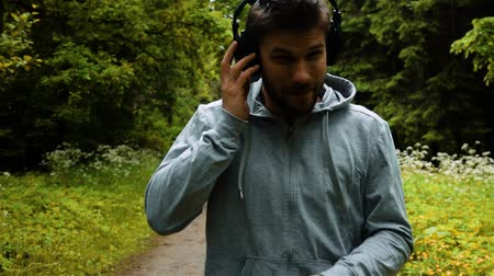 mês : Male runner in warm clothes in autumn park listening to music in bug black headphones and hood clothes. Close-up super slow motion shot.