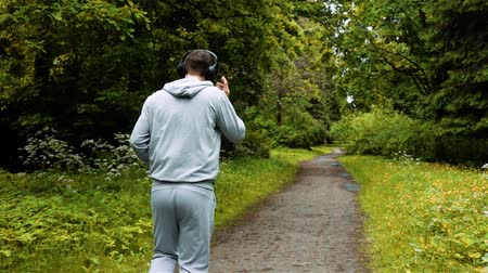 Male runner in warm clothes in autumn park listening to music and hood clothes. Middle shot super slow motion. Big black closed headphones.