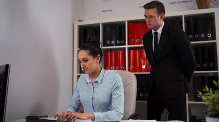 birlik : Businessman in formal suit and tie praises his colleague female employee for a job well done at office with desktop computer PC. Middle shot. Stok Video