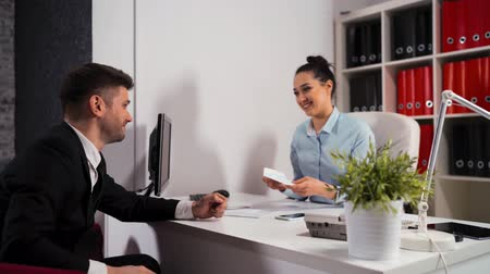 imposto : Business people sign contract in office. Young attractive handsome client give envelope with dollars to manager businesswoman. She count summ and approve deal. Stock Footage
