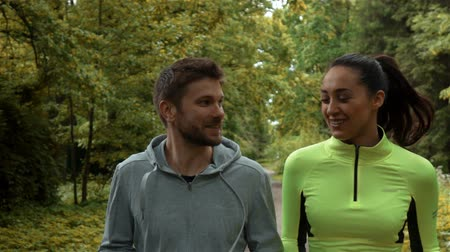 aerobic : Tracking slow-motion of man and woman communicating and smiling during morning jog. Wideo