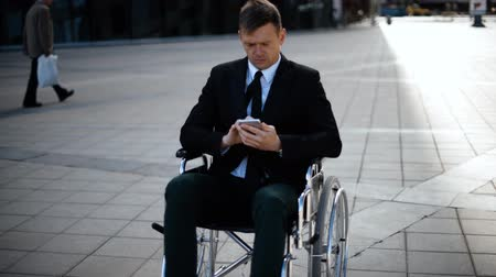 Young attractive entrepreneur business man sitting on wheelchair is playing or working with his smartphone outdoor. Wideo