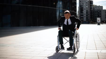 auxiliar : Cripple businessman trying to get up from wheelchair outdoor. He strained angry and disappointed of his aidless. Stock Footage