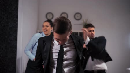 Three joyful employees expressive dancing cheerfully in office in front of the camera. Wideo