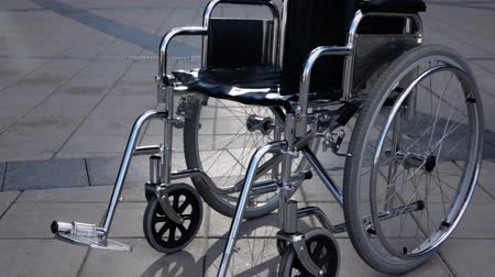 Disabled wheelchair rolling near modern business district. steadicam shot. Imminent illness concept. Disease. Slow motion, Wideo