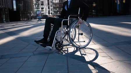 инвалид : Physically disabled invalid businessman. He turning his wheelchair to camera front in super slow motion. Modern glass business district background. Стоковые видеозаписи