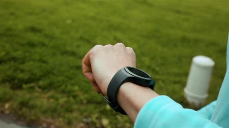 wristband : Runner using smart watch fitness tracker and heart rate monitor jogging on trail in forest. Close-up in super slow motion of smart clock. Close-up.