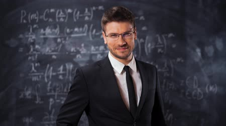 мел : Portrait of scientist man with mathematical equations background. He put on his glasses and smile at camera. Clever and smart teacher lecturer concept. Lets study!