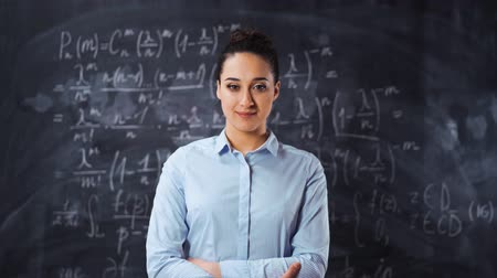 Portrait of young smart clever woman teacher lecturer standing with chalk board full of math equations at background.