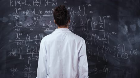 deska : Female student in white robe standing opposite wall chalk board with math equations and formula. She try to solve and prove the theorem. No face. Slider glidetrack camera movement. Back middle shot