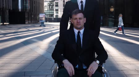инвалид : Young attractive businessman tote his cripple colleague in wheelchair outdoor, near business centre glass building. He looks sad or have no emotions on face. Slow motion sunrise shot.