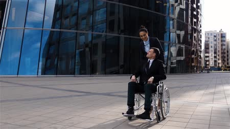 Handsome businesswoman cares for his colleague handicapped cripple businessman in wheelchair.
