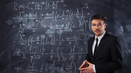 high school : Young handsome male teacher or student in spectacles explaining decision of hard math equation. Stock Footage