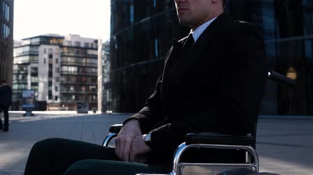 закрытыми глазами : Portrait of handicapped businessman turn his head to camera, wearing formal suit in wheelchair outdoor near modern office building. Teal and orange style. Sunrise.