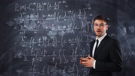 deska : Young caucasian man teacher lecturer in formal suit and tie explaining decision of hard math equation. He invite You to study in university, smile and looks smart and clever.