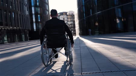 furioso : Back view of a invalid cripple businessman in wheelchai with glass building for business deals at bg. He move in his chair quiet in super slow motion. Camera go back with him smoothly. Wide view