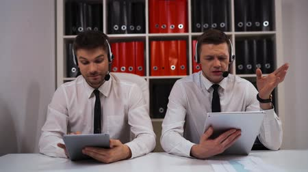 dispatcher : Two call-centre technical support specialist businessmen talking with customers by headsets hands-free. The smile and very polite with clients. Stock Footage
