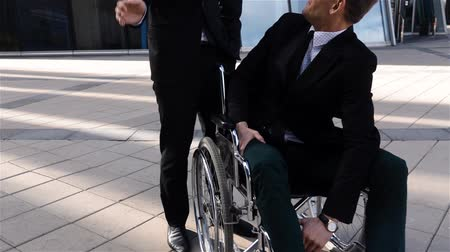 establishment : Happy disabled business man in wheelchair, spending time in business deal district with his friend, smiling and supporting handicapped male good mood and blow to the shoulder. Slow motion