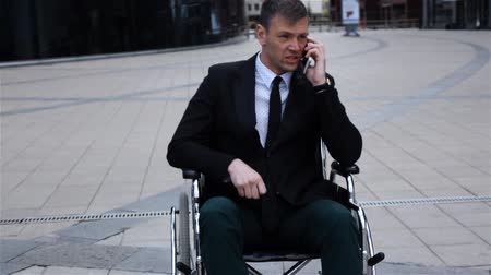 lekarstwo : Disabled Invalid entrepreneur businessman talking by phone sitting in wheelchair outdoor. business theme. Slow motion steadicam. Hard and negative emotion
