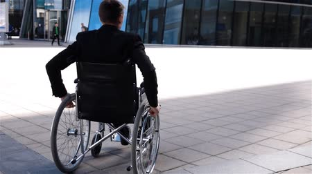 Young disabled businessmman in wheelchair move near modern glass business centre. Back view. Super slow motion shot. Negative emotion with turning head. Formal suit. Wideo