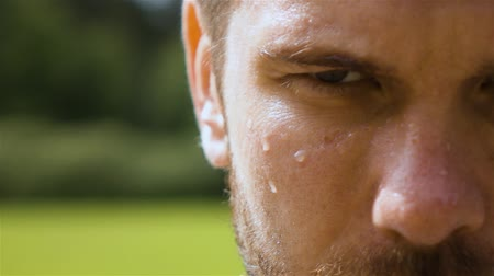 хорошее здоровье : Epic extreme close-up shot of sweaty man outdoor in park. Drop of water on his face macro slow motion.