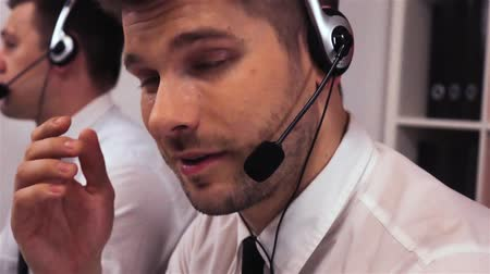 Two employee with headsets talking on voice call-centre. Entrepreneur turn his head to the camera and smiling. He look very happy of his job with his colleague. Super slow motion shot.
