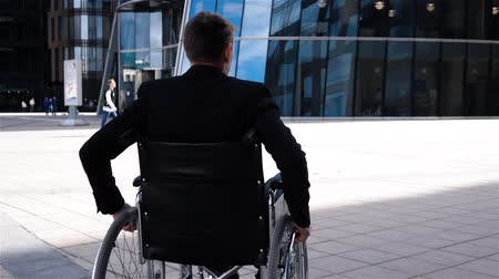 Young handicapped man in wheelchair move near modern glass business centre. Back view.