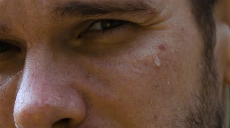 хорошее здоровье : Epic extreme close-up shot. Eye and nose. sweat man outdoor in park. Drop of water on his face