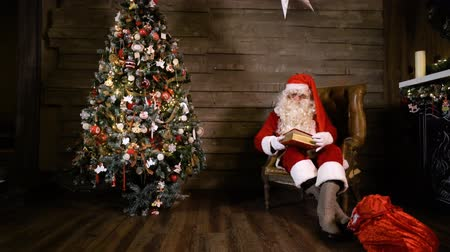 Santa Claus pulling out and Reading Book or photo album near Christmas Tree at Home. A bag with gifts and a fireplace. Wideo