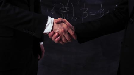 sterlin : Two scientists make handshake closeup with mathematical equations on chalkboard. Super slow motion.