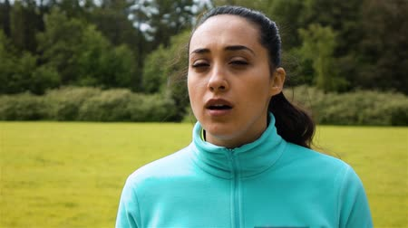 respiração : Female jogger out of hard breath looks around with a subtle smile on her face in super slow motion, epic look in camera. Park background sunny morning.