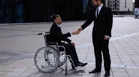 Happy entrepreneur shaking hands with cripple colleague in wheelchair outdoor in slow motion. Sunset or sunrise. Happiness. Fortune and blessing of comfort working and partnership Wideo