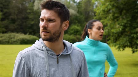 Sport couple relaxing after jogging in city park. Runners exercising - woman and man runner training on run living healthy active lifestyle. Epic turning look at camera. Male at front view.