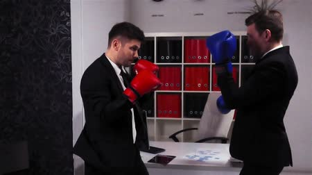 raiva : Boss and employee Boxing in Office Room. Red and blue gloves. Super slow motion shot. Competition and fighting in office concept.