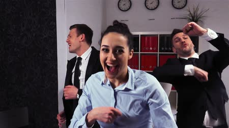 имитация : 2 Crazy happy businessman and businesswoman dancing doing victory dance. Success achievement in super slow motion. Expressive happy emotions.