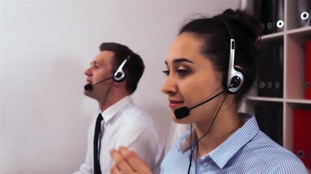 телемаркетинг : Attractive sexy female employee in headset calling to client with smile. A team of call centre executives wearing hands-free busy on a phone with customers.