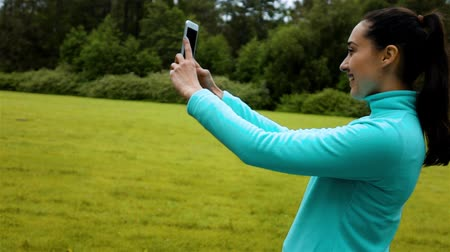 wearing earphones : Female jogger standing on a nature trail and taking a smiling selfie with her phone, early morning green park background. Stock Footage