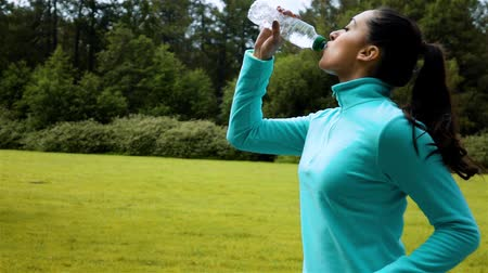 Female runner drinks from a bottle of water while running in green autumn morning park. Super slow motion shot. fatigue and sweat. Profile view. Fresh and cool concept.