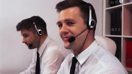 Two men with headsets talking on voice call centre. Businessman turn his head to the camera and smiling.