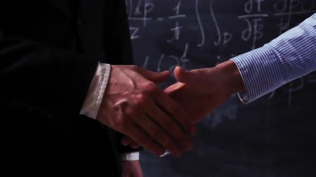 sterlin : Two smart scientists, male and female, make handshake closeup with mathematical equations on chalkboard. Super slow motion.