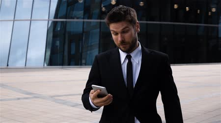 Young businessman texting sms using app on smart phone while walking in city, Happy smiling handsome hispanic man employer using smartphone, wearing suit jacket outdoors, slow motion