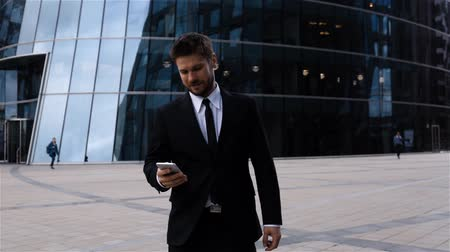 Handsome entrepreneur reading sms using app or messenger on iphone in business centre, smiling attractivehispanic man employer using smartphone.